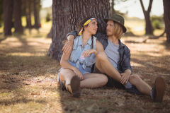 Pares que se sientan en campo por el tronco de árbol Foto de archivo