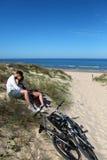 Pares que se sientan en el abarcamiento arenoso de la duna Fotografía de archivo