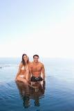 Pares que se sientan en el borde de la piscina con el mar Imagen de archivo