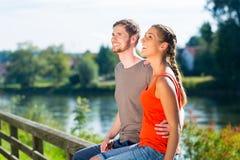 Pares que se sientan en el riverbank en verano Fotografía de archivo
