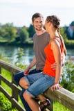 Pares que se sientan en el riverbank en verano Imagenes de archivo