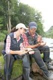 Pares que se sientan en el río con las líneas Fotos de archivo