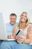 Pares que se sientan en el sofá que hace compras en línea fotografía de archivo libre de regalías