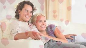 Pares que se sientan en el sofá en sala de estar con los corazones almacen de video