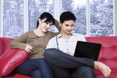 Pares que se sientan en el sofá usando el cuaderno Imagen de archivo libre de regalías