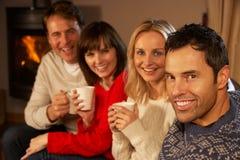 Pares que se sientan en el sofá con hablar caliente de las bebidas Imagenes de archivo