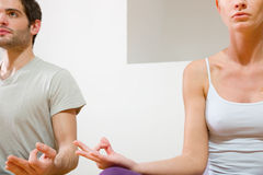 Pares que se sientan en el suelo que hace yoga Fotografía de archivo