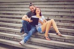 Pares que se sientan en escaleras en el campus universitario Imagen de archivo libre de regalías