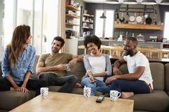 Pares que se sientan en hablar de Sofa With Friends At Home Imagen de archivo libre de regalías
