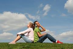 Pares que se sientan en hierba Foto de archivo libre de regalías