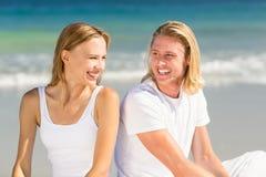 Pares que se sientan en la playa Fotografía de archivo libre de regalías