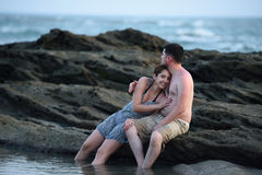 Pares que se sientan en la playa de la roca Imagen de archivo