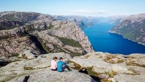 Pares que se sientan en la roca que disfruta de la opini?n del fiordo, cerca de Preikestolen, Noruega foto de archivo