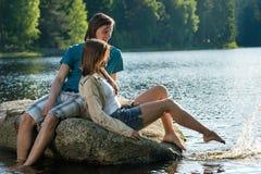 Pares que se sientan en la roca que comparte el momento romántico Fotos de archivo