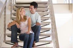 Pares que se sientan en la sonrisa de la escalera Foto de archivo libre de regalías