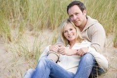 Pares que se sientan en la sonrisa de la playa Fotos de archivo libres de regalías