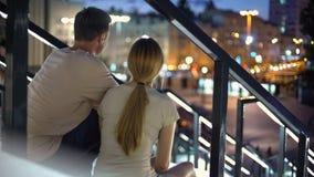 Pares que se sientan en las escaleras, abrazando, observación iluminada igualando la ciudad, amor imagenes de archivo