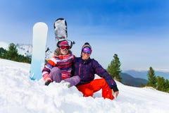 Pares que se sientan en máscaras de esquí en la nieve Imagen de archivo libre de regalías