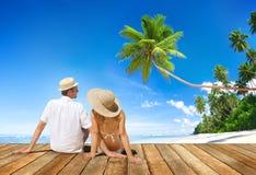 Pares que se sientan en piso de madera en la playa imágenes de archivo libres de regalías