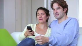 Pares que se sientan en Sofa Watching TV junto metrajes