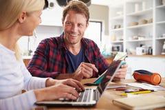 Pares que se sientan en su cocina usando el ordenador portátil Imagen de archivo