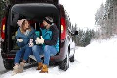 Pares que se sientan en tronco de coche abierto por completo del equipaje cerca del camino, espacio para el texto Invierno fotografía de archivo