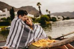 Pares que se sientan en un barco en una fecha romántica imagenes de archivo