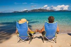 Pares que se sientan en una playa Imagen de archivo libre de regalías