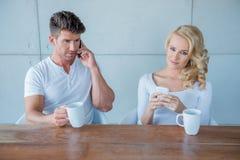Pares que se sientan que comen café con los teléfonos móviles Imagen de archivo libre de regalías