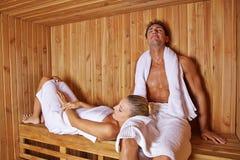 Pares que se sientan y que ponen en sauna Foto de archivo