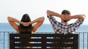 Pares que sentam-se em um banco e que relaxam filme