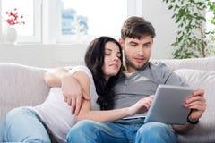 Pares que sentam-se em um sofá com tablet pc Imagens de Stock