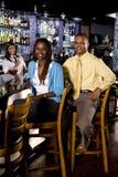 Pares que sentam-se em uma barra Fotografia de Stock Royalty Free