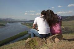 Pares que sentam-se em uma rocha nas montanhas Fotografia de Stock Royalty Free