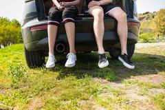 Pares que sentam-se na bagageira do carro no campo verde Fotografia de Stock Royalty Free