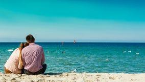 Pares que sentam-se na opinião traseira da praia Imagem de Stock