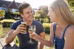 Pares que sentam-se na tabela que aprecia a bebida exterior do verão no bar fotografia de stock