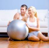 Pares que sentam-se no assoalho com a esfera de prata do exercício Fotos de Stock Royalty Free