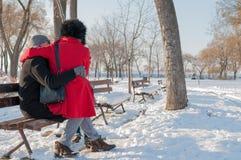 Pares que sentam-se no banco no inverno Imagem de Stock Royalty Free
