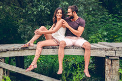 Pares que sentam-se no cais e no afago Fotos de Stock Royalty Free