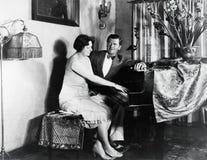 Pares que sentam-se no piano (todas as pessoas descritas não são umas vivas mais longo e nenhuma propriedade existe Garantias do  imagem de stock royalty free