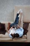 Pares que sentam-se no sofá Imagens de Stock