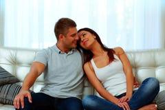 Pares que sentam-se no sofá junto Fotografia de Stock Royalty Free