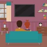 Pares que sentam-se no sofá que olha a tevê Fotografia de Stock