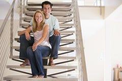 Pares que sentam-se no sorriso da escadaria fotos de stock royalty free