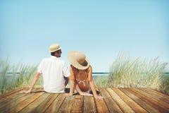 Pares que sientan concepto cómodo del día de fiesta de la hierba de la playa fotos de archivo libres de regalías