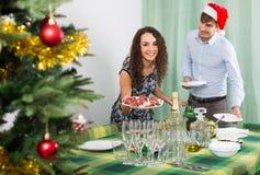 Pares que sirven la tabla del Año Nuevo junto Foto de archivo