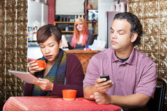 Pares que Sneaking com dispositivos de Digitas Fotografia de Stock Royalty Free
