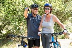 Pares que sonríen con su bici Imagen de archivo