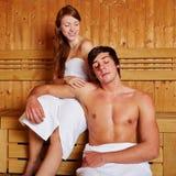 Pares que sonríen en sauna Fotos de archivo libres de regalías